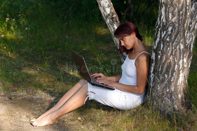 Kobieta z laptopem pod brzozy drzewem obraz stock