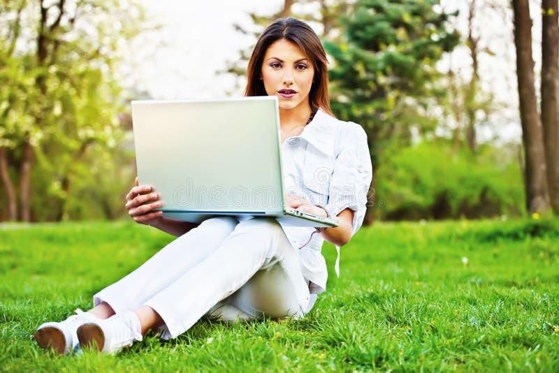 Kobieta z laptopem w parku zdjęcie royalty free