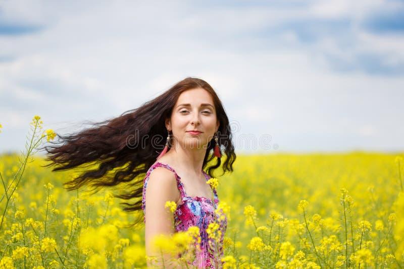 Kobieta z latającym włosy na żółtym gwałta polu fotografia stock