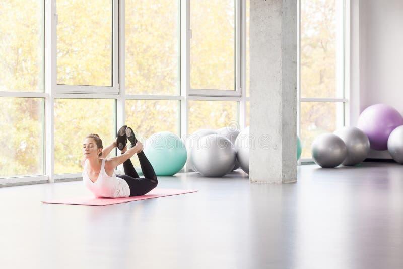 Kobieta z małym uśmiechem robi joga, łęk postura, joga DhanurÄ  s zdjęcia royalty free