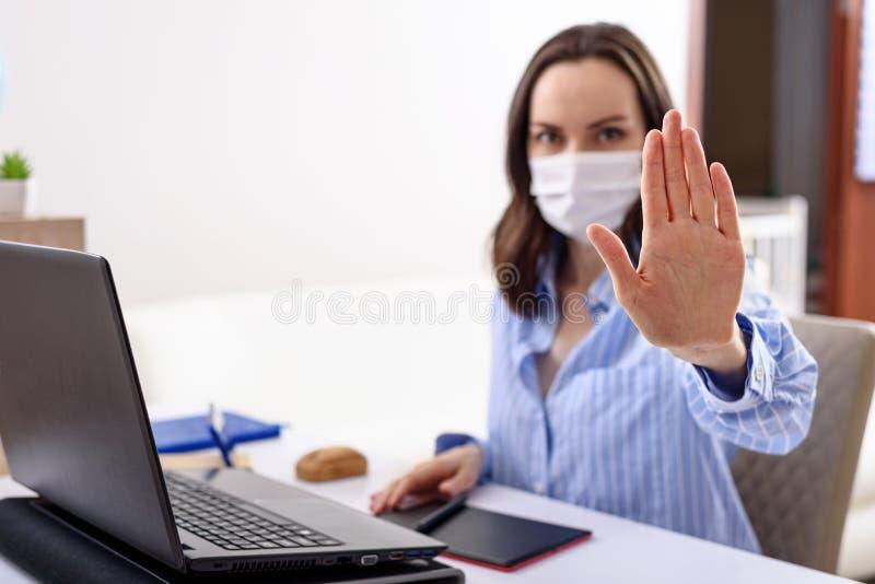 Kobieta z maską medyczną na twarzy zatrzymuje się z ręką podczas siedzenia na laptopie, zdalnej pracy w kwarantannie, koncepcji u obraz royalty free
