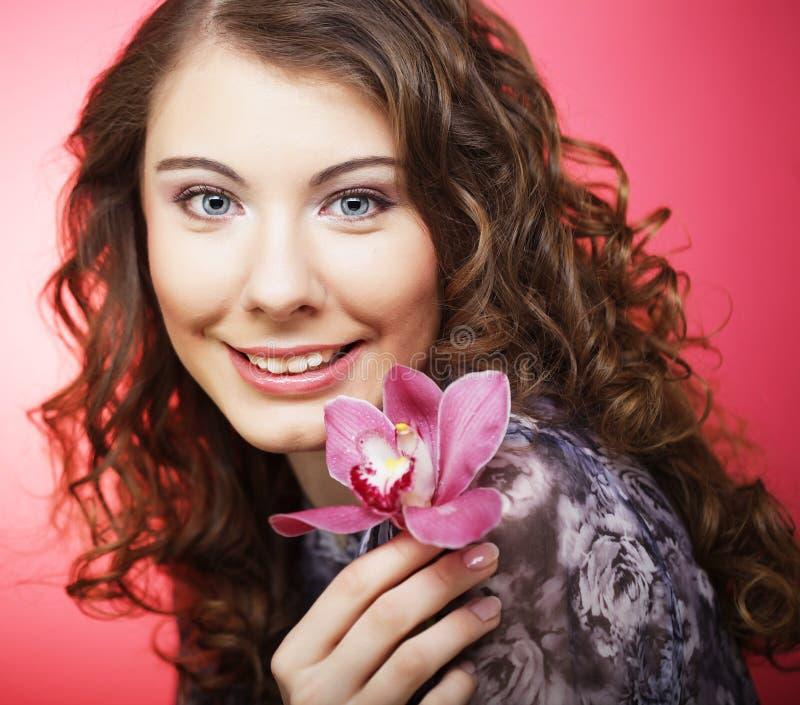 Kobieta z menchia kwiatem nad różowym tłem fotografia royalty free