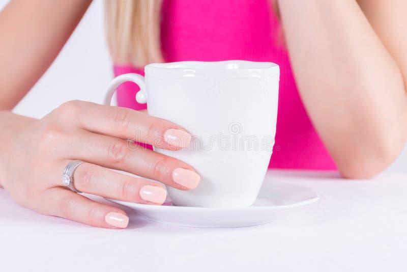 Kobieta z nagim koloru manicure'u gwoździ połysku gel i diamentowymi pierścionkami na palcowej trzyma filiżance zdjęcie stock