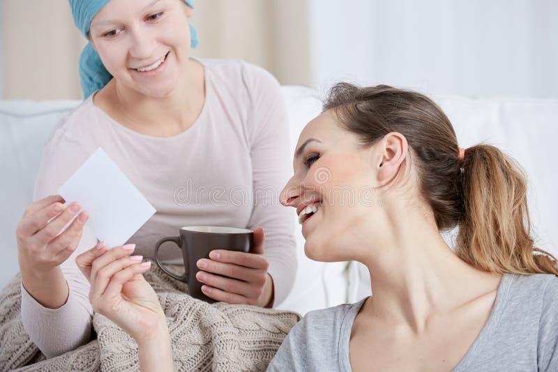 Kobieta z nowotworem i jej przyjaciel patrzeje fotografię fotografia royalty free