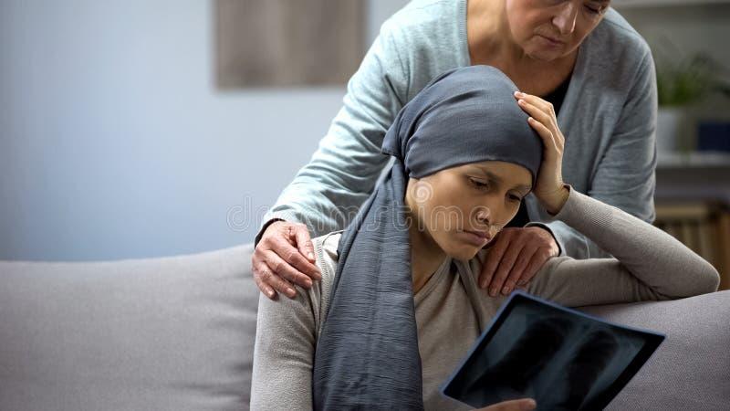 Kobieta z nowotworem patrzeje promieniowanie rentgenowskie, macierzysta podporowa c?rka, marnienie obrazy stock