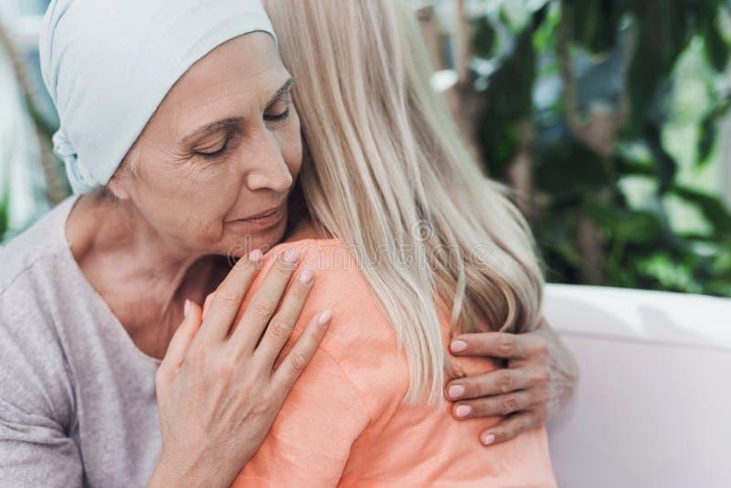 Kobieta z nowotworem siedzi na białej kanapie obok jej córki Dziewczyna ściska kobiety zdjęcie stock