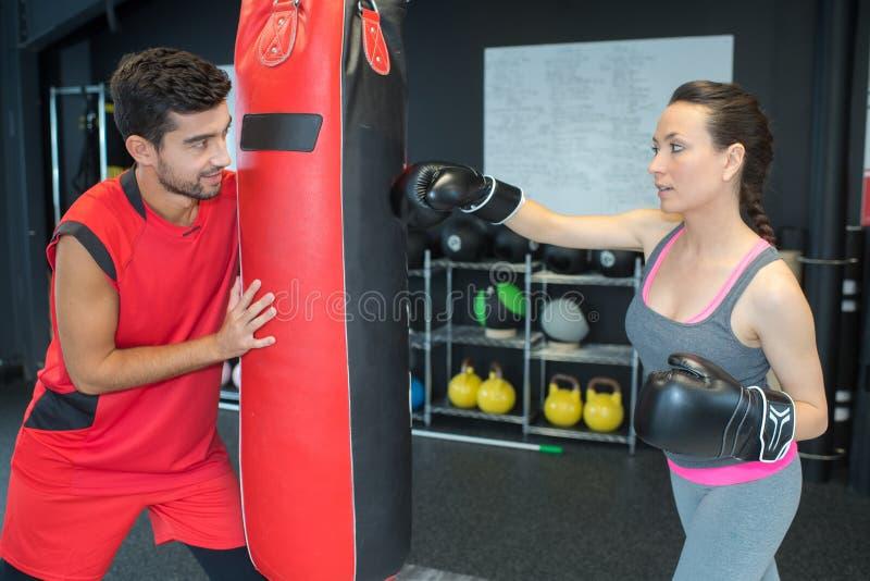 Kobieta z osobistym trenera boksem w gym zdjęcie royalty free