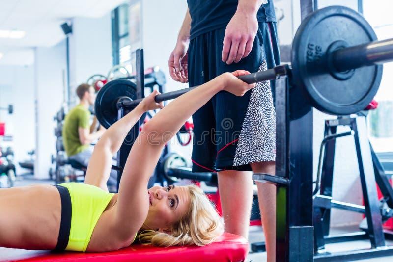 Kobieta z osobistym trenerem przy ławki spotkanie z prasą gym zdjęcie royalty free