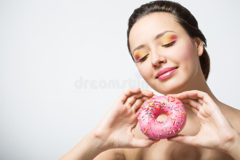 Kobieta z pączkiem i jaskrawym makeup zdjęcie royalty free