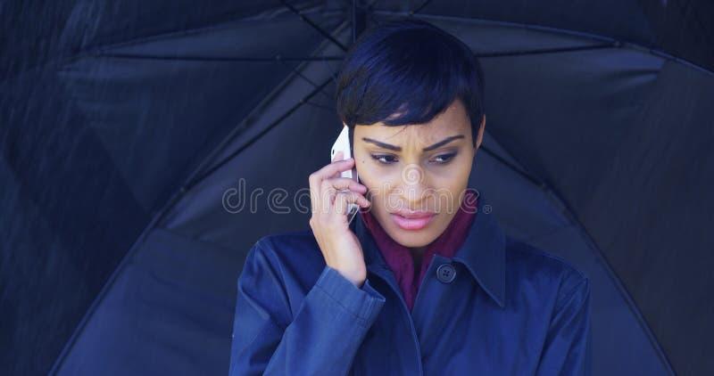 Kobieta z parasolową pozycją w podeszczowym używa telefonie komórkowym fotografia royalty free