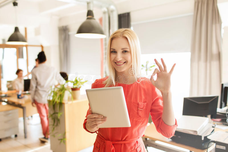 Kobieta z pastylka komputerem osobistym pokazuje ok znaka przy biurem obrazy stock