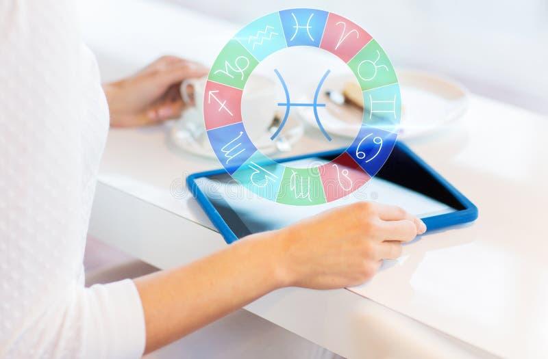 Kobieta z pastylka zodiakiem i komputerem osobistym podpisuje przy kawiarnią fotografia stock
