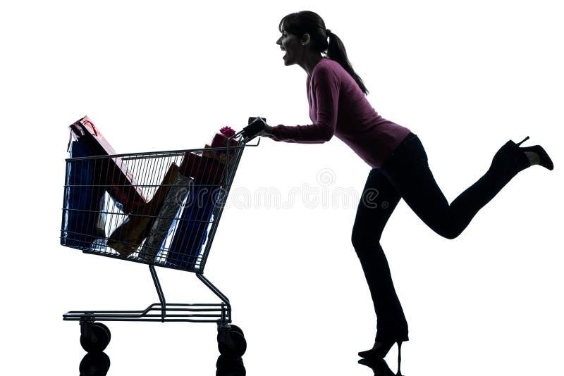 Kobieta z pełną wózek na zakupy sylwetką fotografia royalty free
