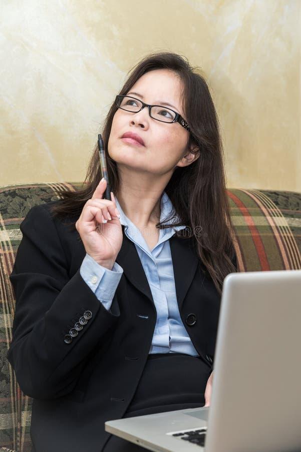 Kobieta z piórem i laptop na kanapie obraz royalty free
