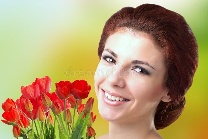 Kobieta z Pięknego bukieta świeżymi czerwonymi tulipanami fotografia royalty free