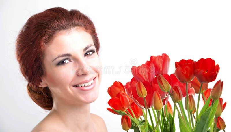 Kobieta z Pięknego bukieta świeżymi czerwonymi tulipanami zdjęcie stock