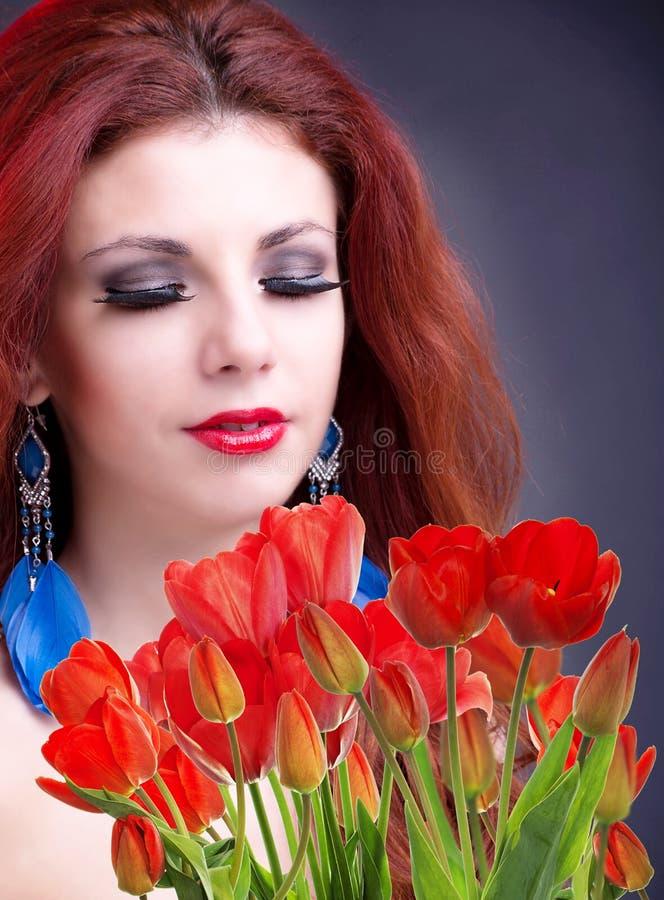 Kobieta z Pięknego bukieta świeżymi czerwonymi tulipanami fotografia stock