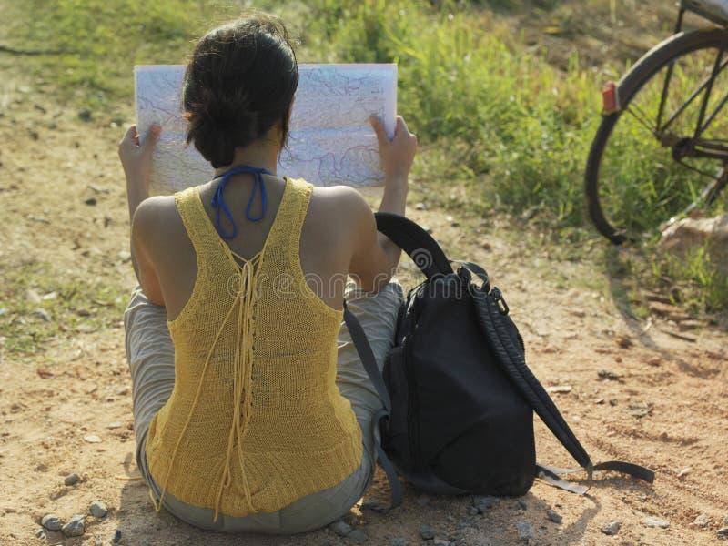 Kobieta Z plecaka I mapy obsiadaniem W Dirtroad obraz royalty free