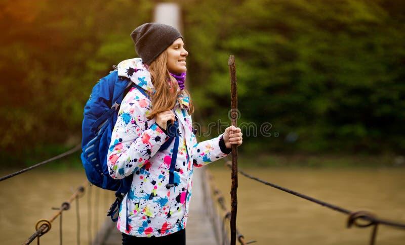 Kobieta z plecakiem wędrującym po leśnym, aktywnym lesie konceptualnym stylu życia i krzyżującym się rzeką zdjęcie stock