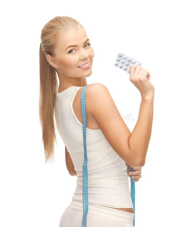 Kobieta z pomiarowymi taśmy i diety pigułkami obrazy stock