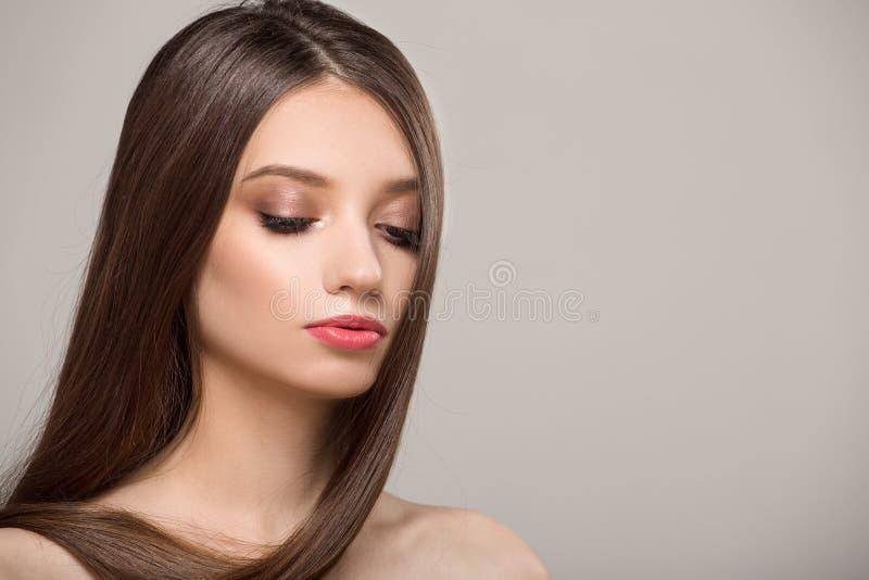 Kobieta z prostym błyszczącym włosy Szary t?o fotografia royalty free