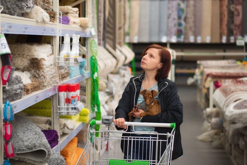 Kobieta z psem w ona r?ki i w?zek na zakupy w dywanowym sklepie zdjęcie royalty free