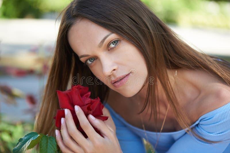 Kobieta z różowym kwiatem w parku obraz stock