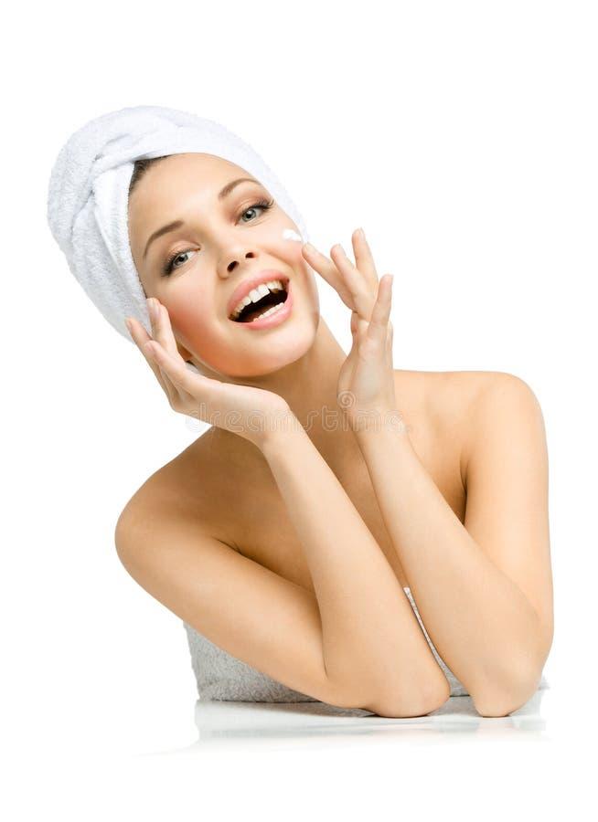 Kobieta z ręcznikiem na głowie stosuje śmietankę na twarzy obraz royalty free
