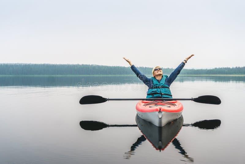 Kobieta z rękami up niezwykle cieszy się calmness jezioro od zdjęcia stock