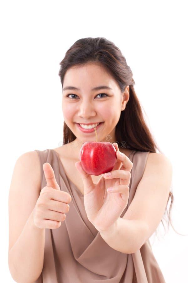 Kobieta z ręki mienia czerwonym jabłkiem, daje kciukowi up zdjęcie stock