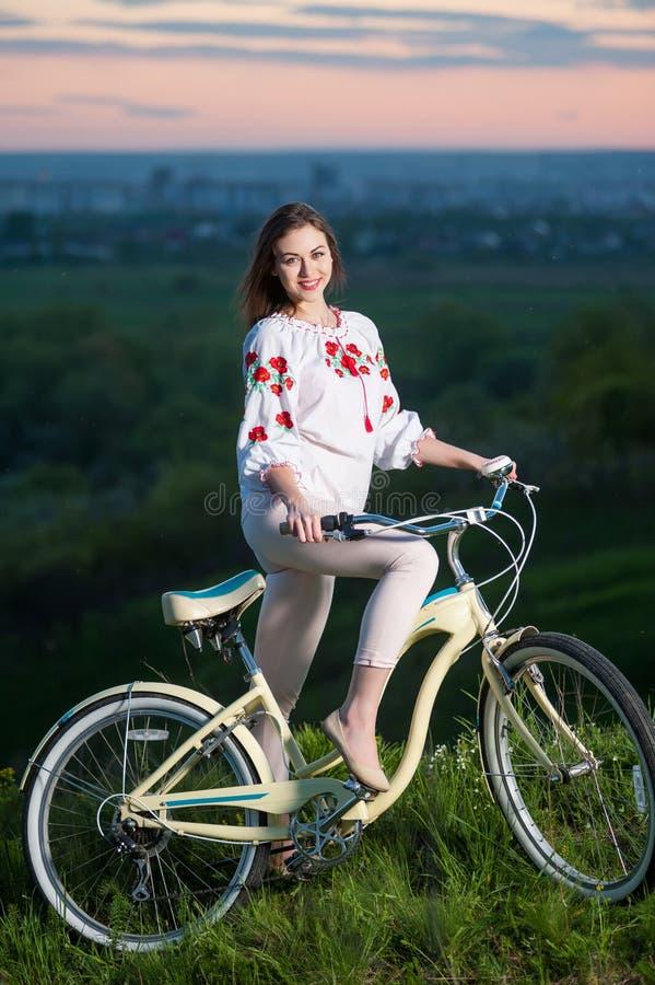 Kobieta z retro rowerem na wzgórzu w wieczór obraz stock