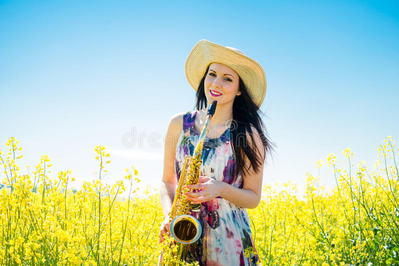 Kobieta z saksofonem w rapeseed polu obraz stock