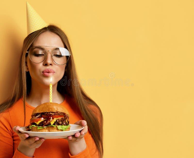 Kobieta z smakowitą dużą wołowina hamburgeru grilla kanapką dla przyjęcia urodzinowego z zaświecającą świeczką na pastelowym kolo obraz stock