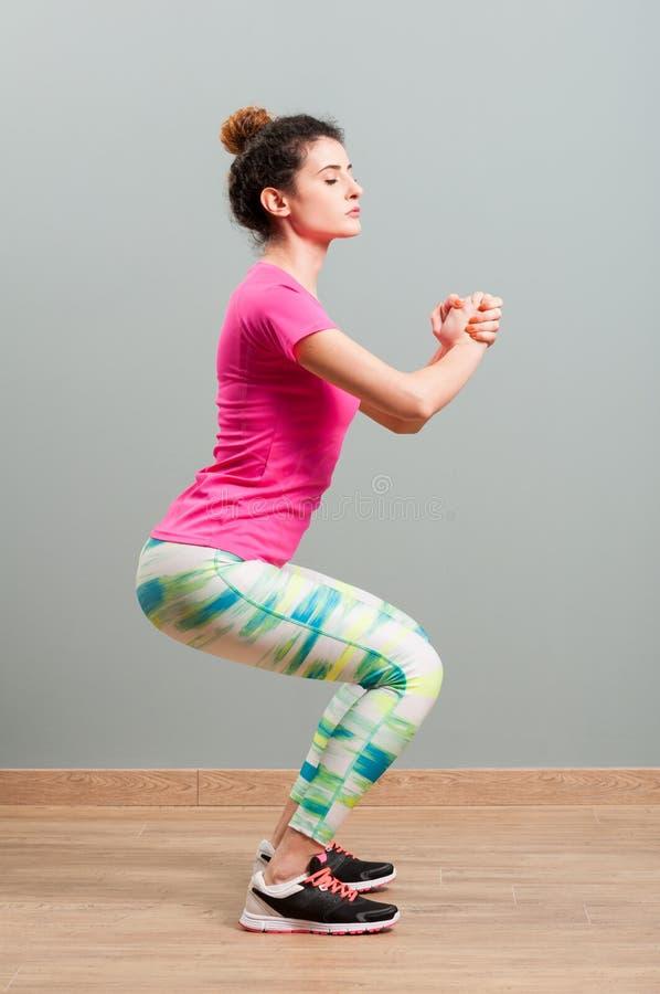 Kobieta z sportswear kształtować jej ciało i kucaniem fotografia royalty free
