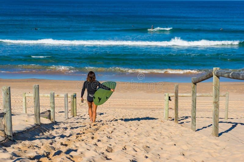 Kobieta z surfing deski odprowadzeniem na piaskowatej plaży fotografia stock