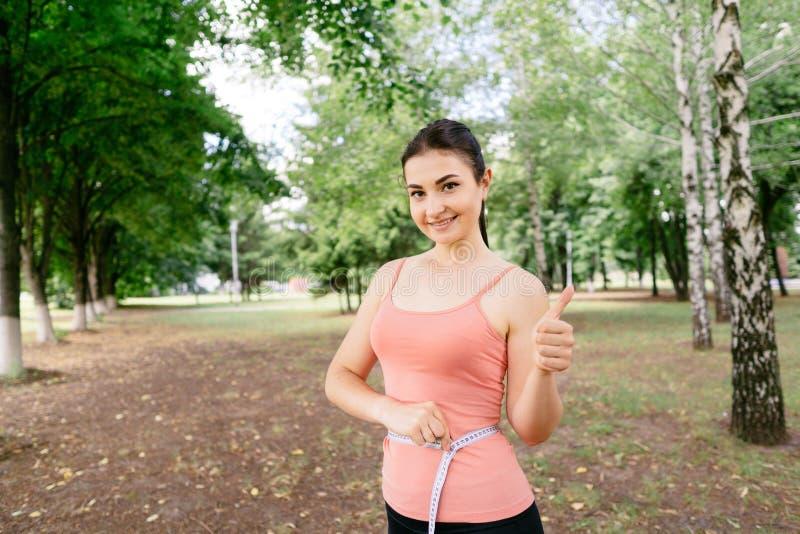 Kobieta z szczupłym ciałem mierzy jej talię zdjęcia royalty free
