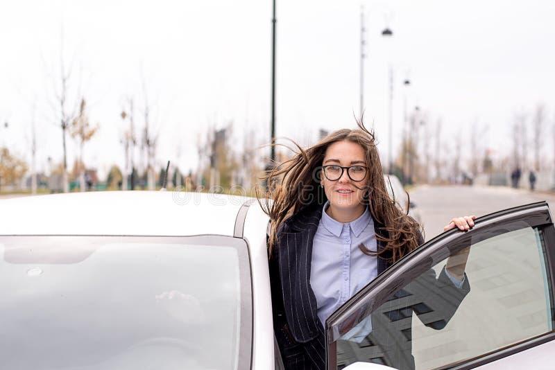 Kobieta z szkłami, błękitną koszula i żakietem, siedzi w samochodzie fotografia stock