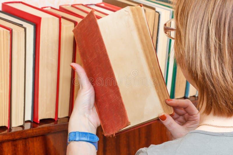 Kobieta z szkłami bierze starą książkę od półka na książki dużo obrazy royalty free