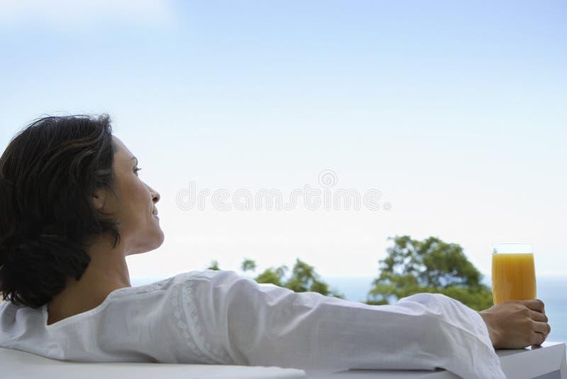 Kobieta Z szkłem sok pomarańczowy W karle zdjęcia royalty free