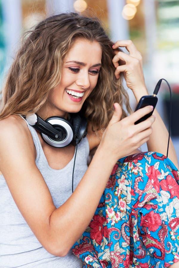 Kobieta z telefonem komórkowym i hełmofonami zdjęcie royalty free