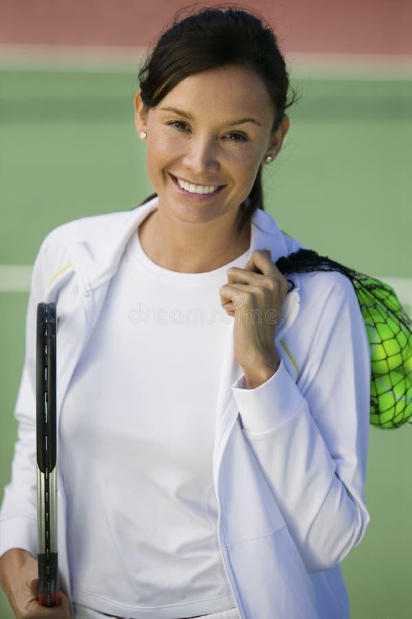 Kobieta z tenisowymi piłkami i kant pozycja na tenisowego sądu portrecie obrazy royalty free