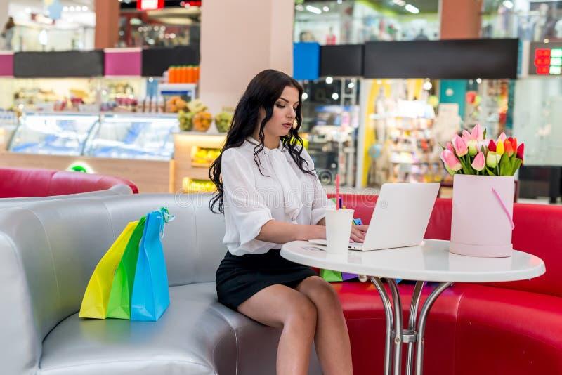 Kobieta z torba na zakupy i laptopem zdjęcia stock