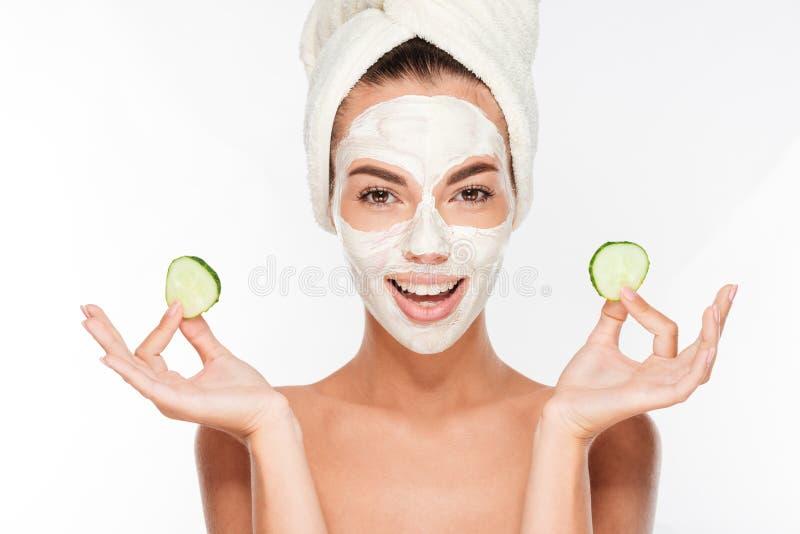 Kobieta z twarzowymi maski i ogórka plasterkami w jej rękach obraz stock