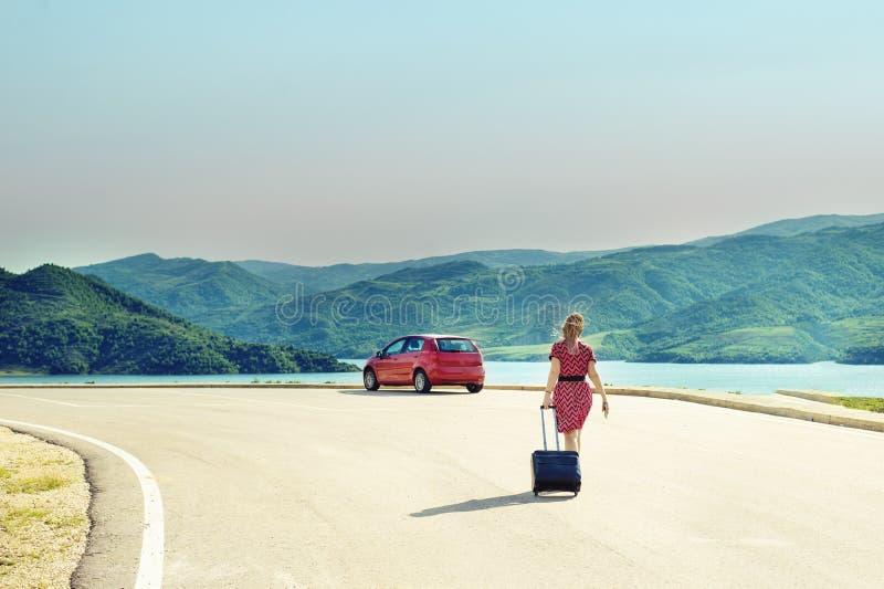 Kobieta z walizką przy drogą z czerwonym samochodem obraz royalty free