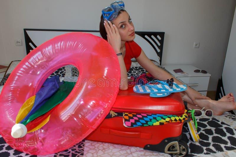 Kobieta z walizki obsiadaniem na łóżku w hotelu Dostawać przygotowywający dla podróżować t zdjęcie royalty free