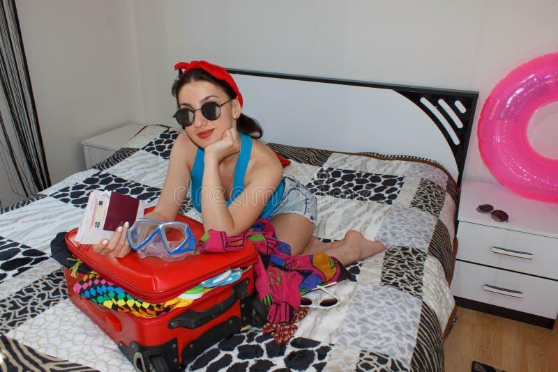 Kobieta z walizki obsiadaniem na łóżku w hotelu Piękna dziewczyna z walizki Czerwonymi miłość podróżować fotografia stock
