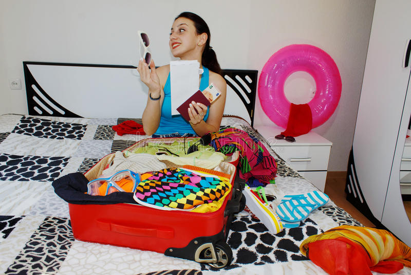 Kobieta z walizki obsiadaniem na łóżku w hotelu Z piękna dziewczyna obraz royalty free