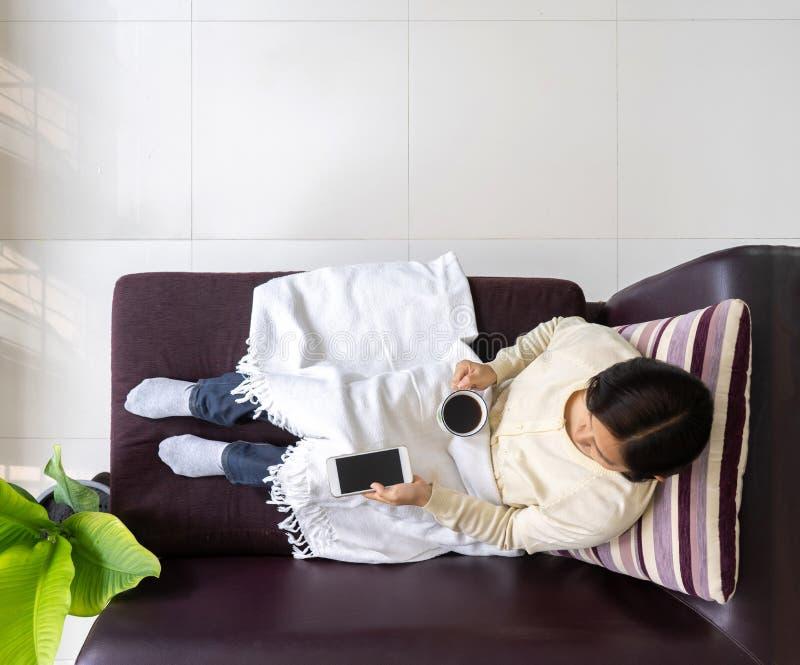 Kobieta z widokiem na oczy relaksująca się w sofie i pijąca kawę fotografia royalty free