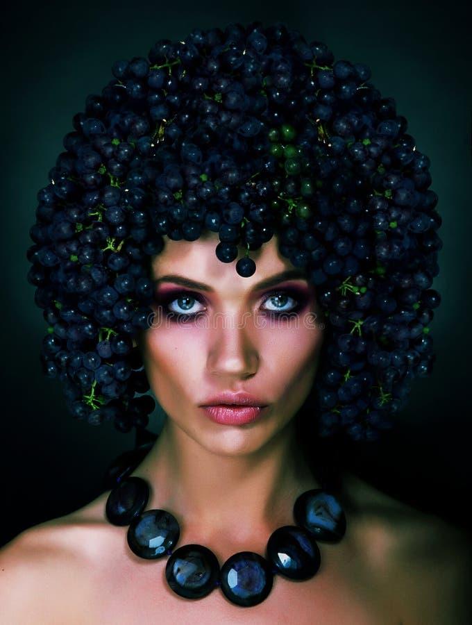 Portret jesieni kobieta z winogronami na ona Kierownicza. Modna fryzura zdjęcia stock
