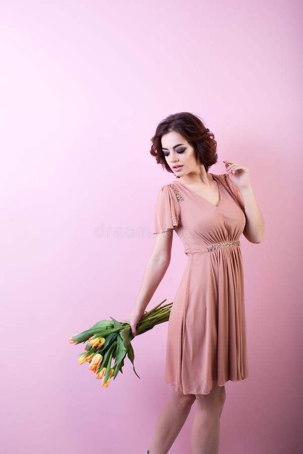 Kobieta z wiosna kwiatu bukietem nad różowym tłem zdjęcia stock